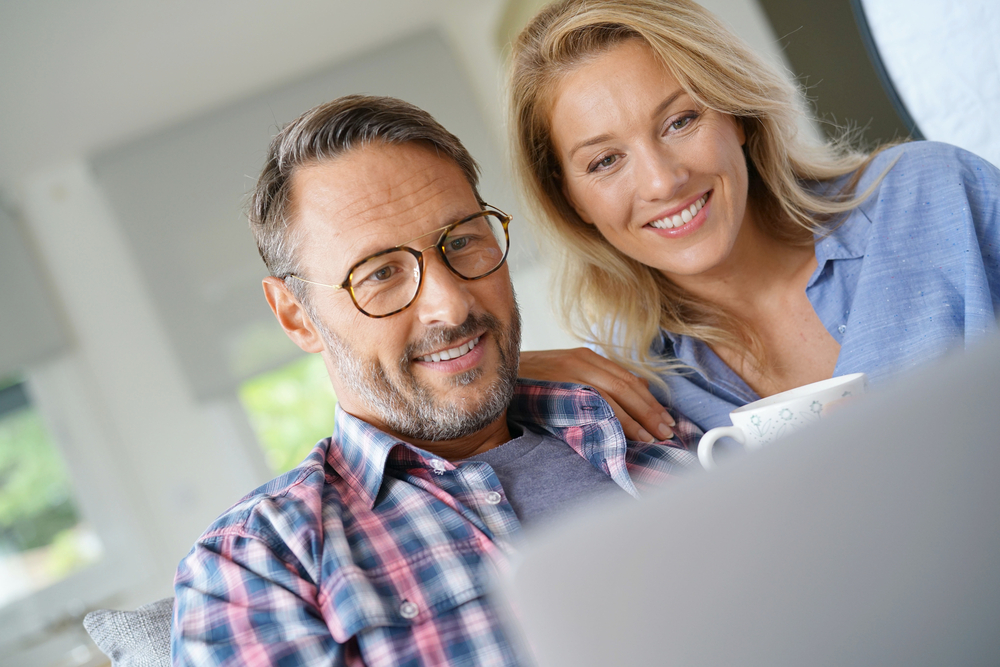 Couple looking at computer with coffee cup, real estate search