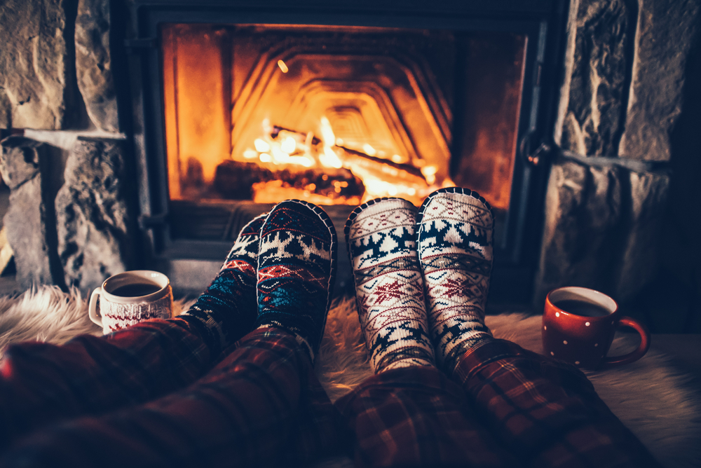 Two people sitting in front of fire, socks, mugs – How to make holiday renters welcome