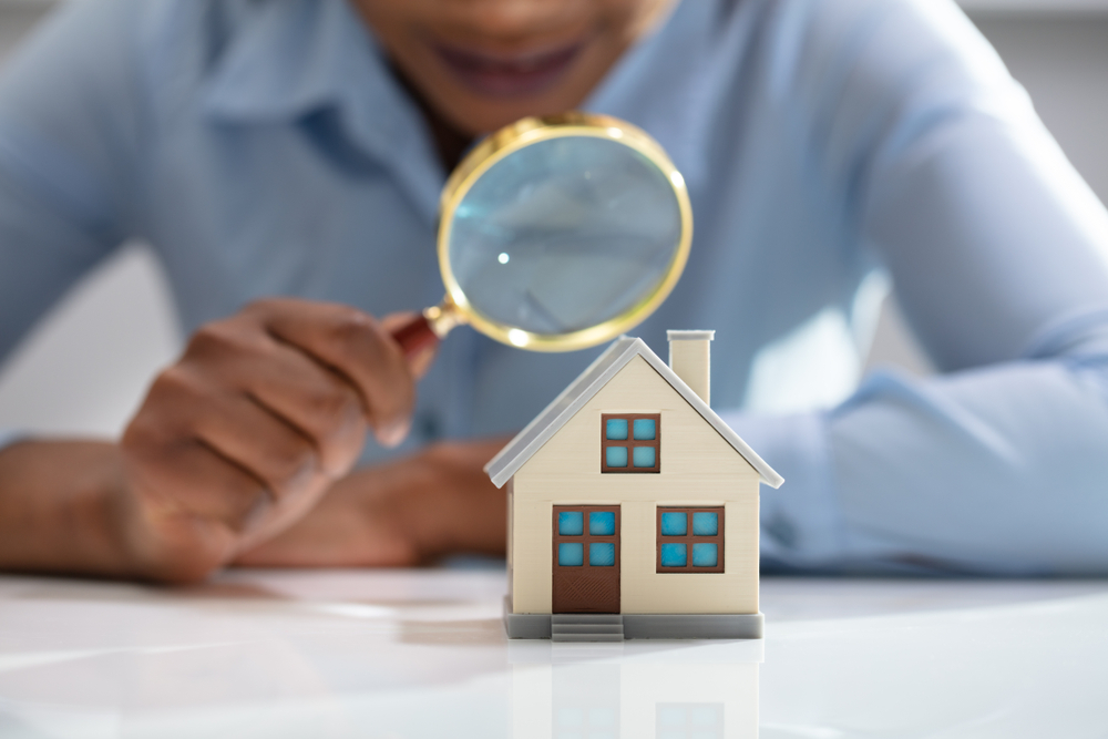 Close up, investor with magnifying glass over home - Gregory M Russell, Equity Loans