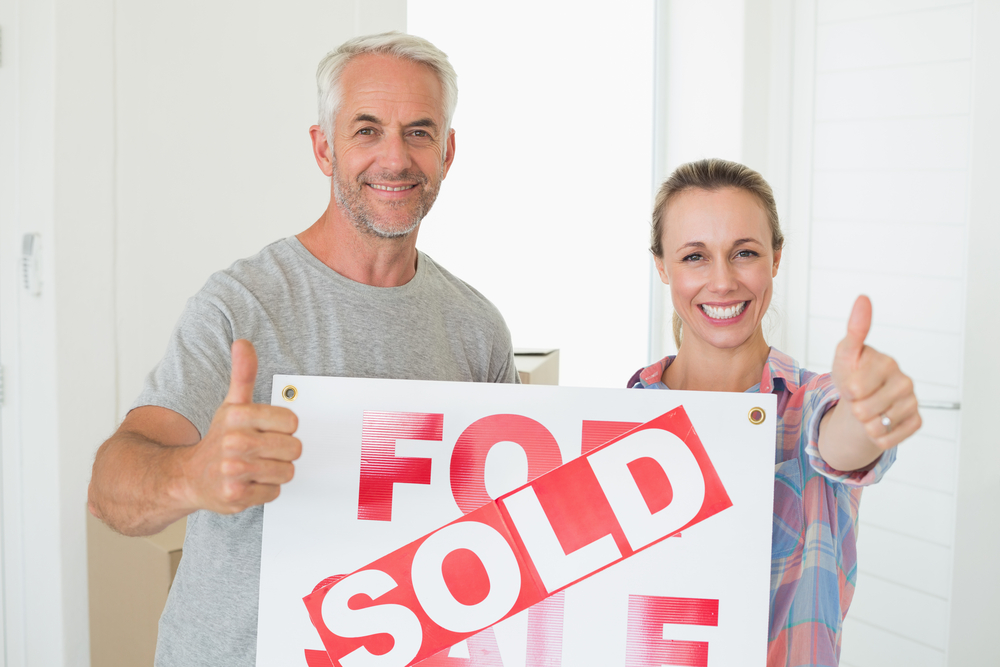 Happy couple, sold sign, home sale