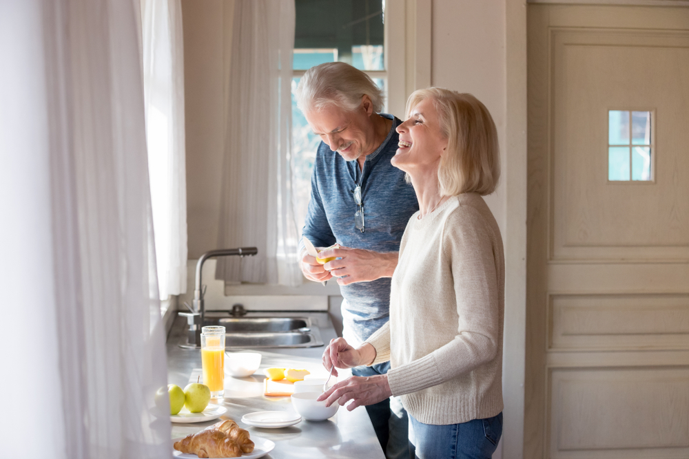 Happy retired couple in kitchen, property upgrades
