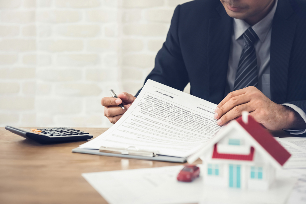 man at desk, signing contract, house, calculator