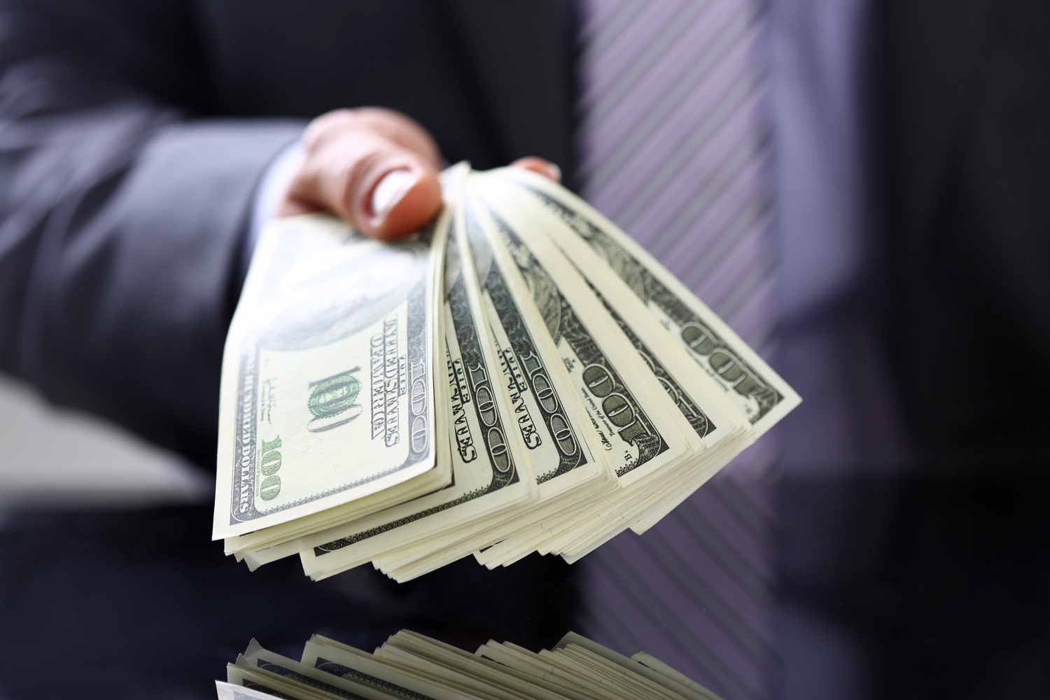 Man in suit, holding cash, closeup, hard money lender