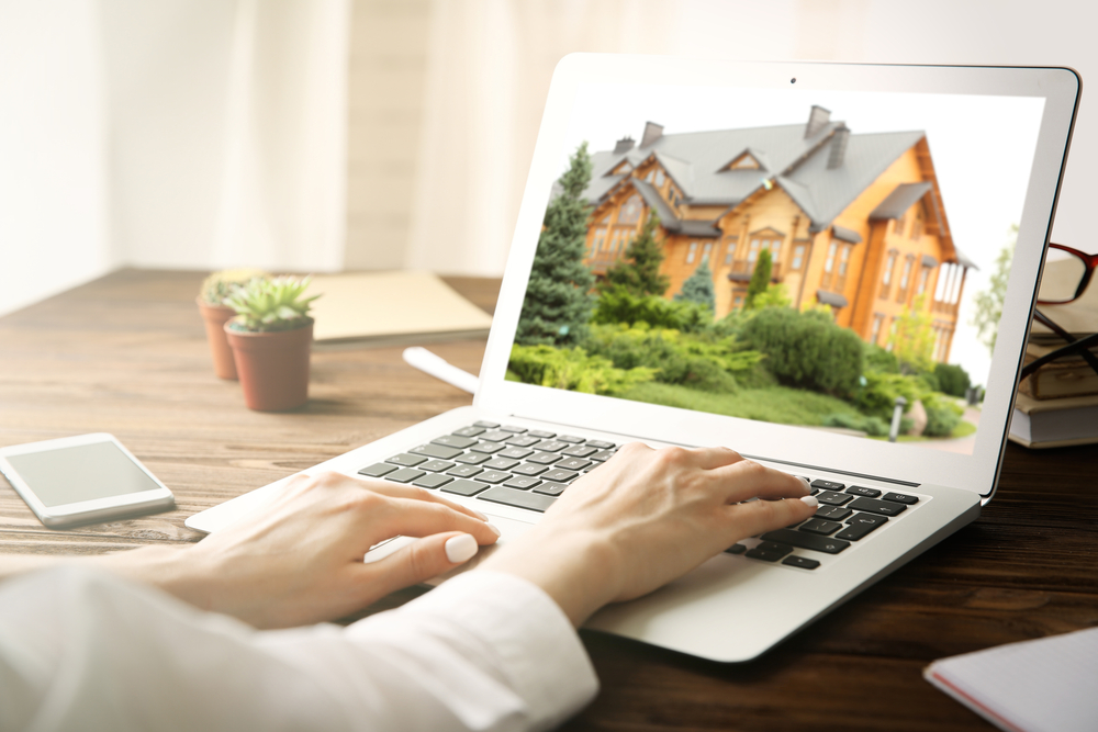person searching for real estate listing on laptop