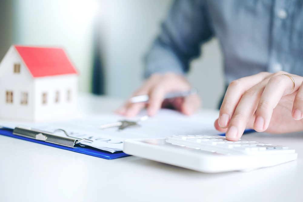 Person using calculator, clipboard, house – How to budget home renovation