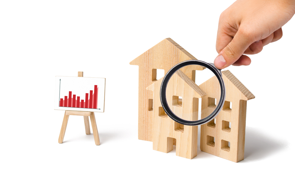 real estate trend chart, model houses, hand with magnifying glass