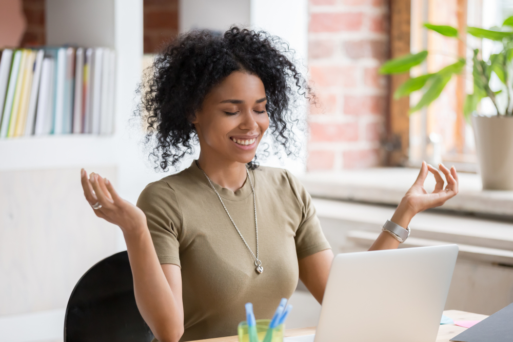 woman searching real estate at computer practicing relaxation