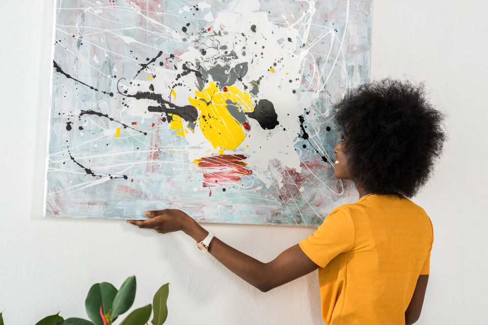 woman hanging painting on wall