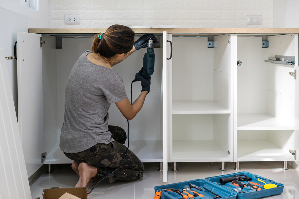 woman installing kitchen cabinets, remodel
