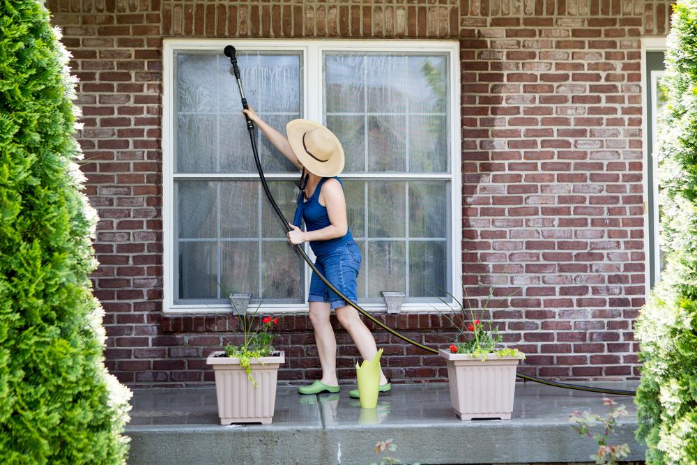 woman washing windows, rental property, spring cleaning